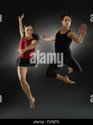 Hispanic dancers leaping in mid-air - Stock Photo