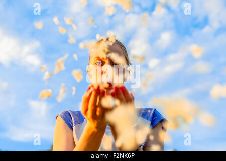 Caucasian teenage girl blowing flower petals under blue sky - Stock Photo