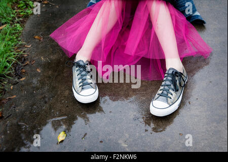 Caucasian girl wearing sneakers and tutu in puddle - Stock Photo