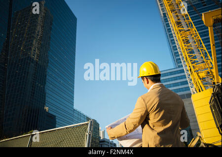 Mixed race architect reading blueprints at construction site - Stock Photo