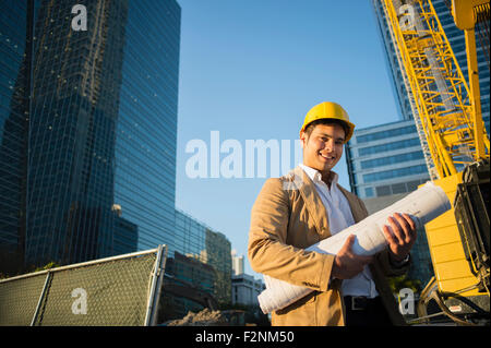 Mixed race architect holding blueprints at construction site - Stock Photo