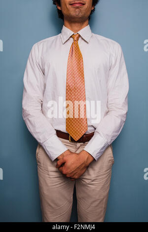 Young man standing by a blue wall, he is wearing a tie - Stock Photo