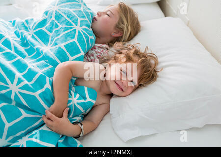 Caucasian brother and sister laying in bed - Stock Photo