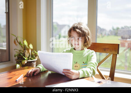Caucasian girl reading papers at table - Stock Photo