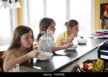 Caucasian sisters eating breakfast in kitchen - Stock Photo