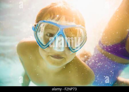 Caucasian boy swimming underwater in swimming pool - Stock Photo