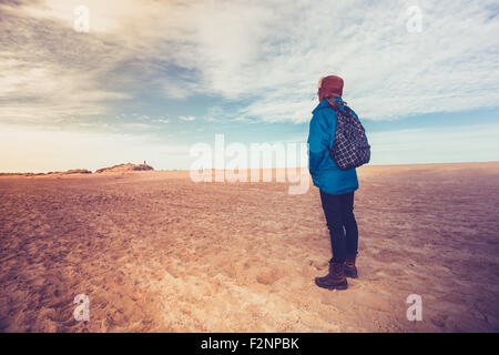 Woman hiking across beach - Stock Photo