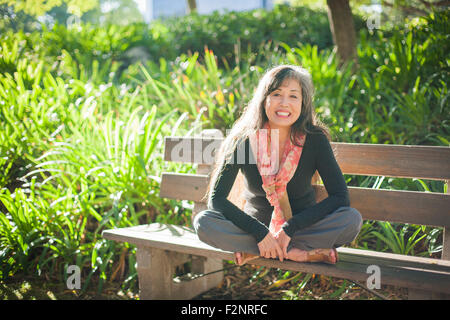 Japanese woman sitting on park bench - Stock Photo