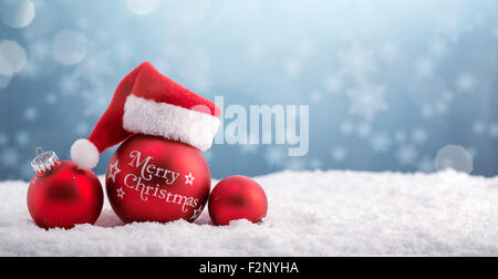 Christmas balls in the hat of Santa Claus on snow. - Stock Photo