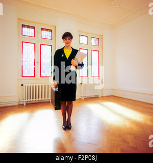 Real estate agent standing in an empty sunny room - Stock Photo