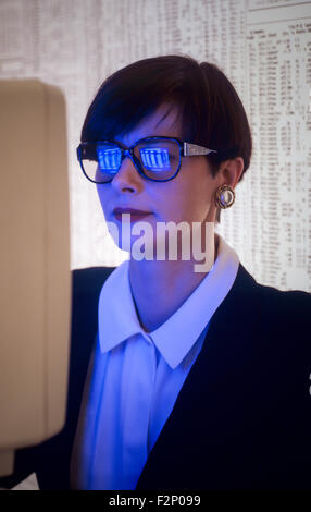 Businesswoman woman with computer screen reflected in her glasses - Stock Photo