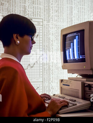 Businesswoman studying statistics graph on computer and stock market composite transactions listing background - Stock Photo