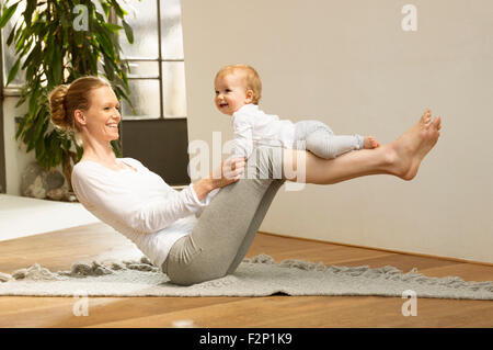 Woman balancing baby on her legs - Stock Photo