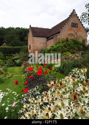 Portrait view of Chenies Manor Pavilion and sunken garden with paths through red and colourful dahlias and sea holly. - Stock Photo