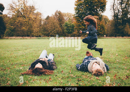 Young parents lying on a meadow while little girl jumping over them in a park - Stock Photo