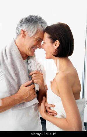 Happy couple with towels head to head in front of white background - Stock Photo