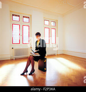 Real estate agent sitting on her briefcase in an empty room - Stock Photo