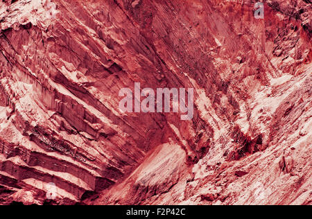 Red fantastic slope with layered texture as abstract background.Toned image. - Stock Photo