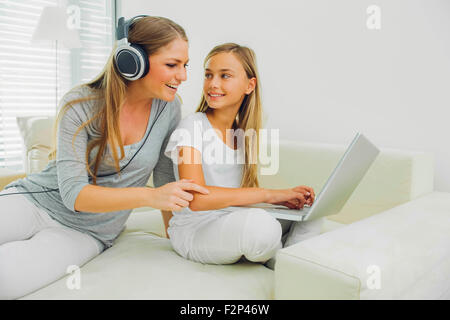 Mother and daughter on couch with laptop and headphones - Stock Photo