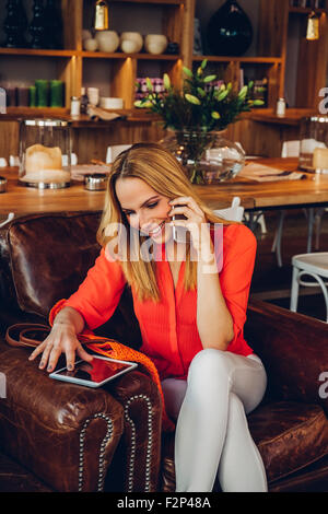 Blond woman with digital tablet sitting in a coffee shop telephoning with smartphone - Stock Photo