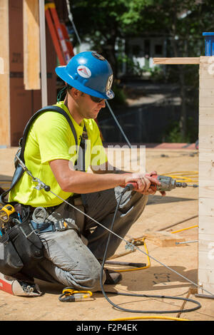 Construction workers uses electric drill to drive screw - Stock Photo