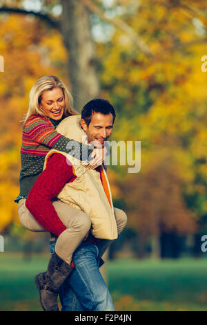 Man giving his girlfriend piggyback in the autumn park - Stock Photo