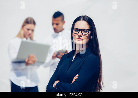 Portrait of stylish young woman with crossed arms wearing glasses - Stock Photo