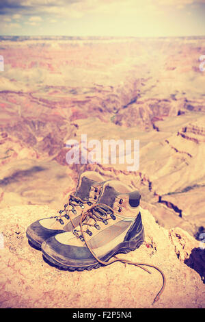 Vintage toned old trekking shoes standing on south rim of Grand Canyon, adventure concept photo. - Stock Photo
