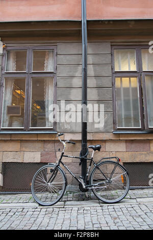 Black bicycle chained to a lamp post outside an old stone building in the Södermalm district of Stockholm - Stock Photo