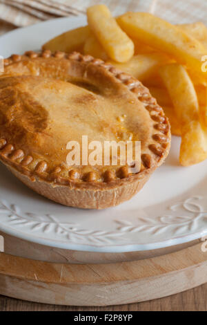 Savoury meat pie with chips or French fries - Stock Photo