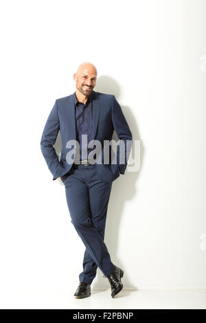 Portrait of bald man with beard wearing blue suit in front of white background - Stock Photo