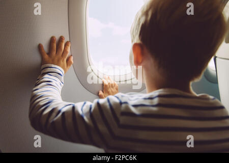 Little boy looking out of window while flying on an airplane - Stock Photo