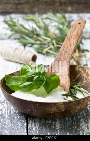 sea salt with fresh herbs: basil, rosemary on a wooden background - Stock Photo