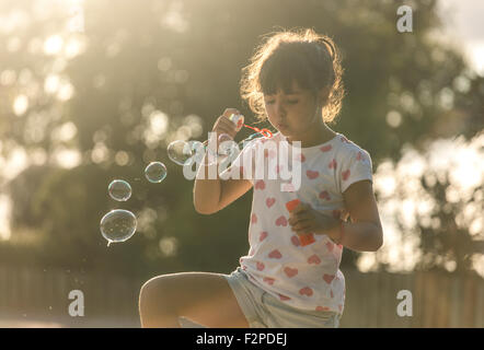 Little girl making soap bubbles in the park at twilight - Stock Photo