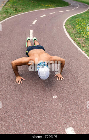 Athletic young man doing pushups in the park - Stock Photo