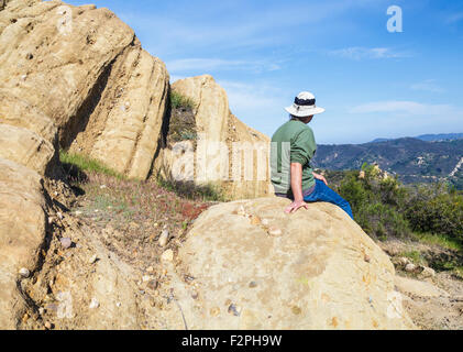Hiker relaxes on rock formations along the Red Rock Trail  in Red Rock Canyon Park in Topanga, California - Stock Photo