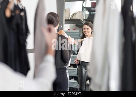 Woman holding top looking in mirror in a boutique - Stock Photo