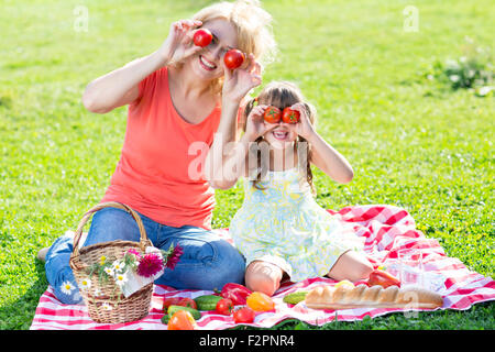 Family having fun while picnicking in the park - Stock Photo