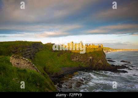 Sunrise over Dunluce Castle along northern coast of County Antrim, Northern Ireland, UK - Stock Photo