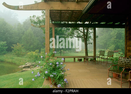 Summer mist surrounds gardens and view from private deck on lake, Missouri, USA - Stock Photo