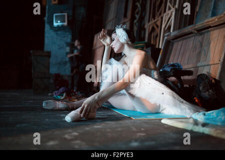 Ballerina sitting on the warm-up backstage - Stock Photo