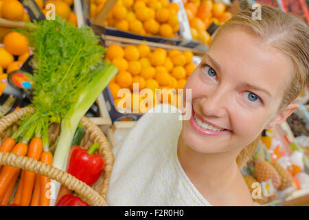 Woman showing basket of vegetables - Stock Photo
