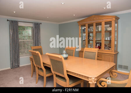 Dining room interior with a large wooden table, chairs, and china cabinet. - Stock Photo