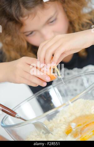Child breaking egg into bowl - Stock Photo