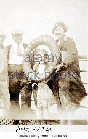fading family snap from 1926 on ship with life preserver - Stock Photo