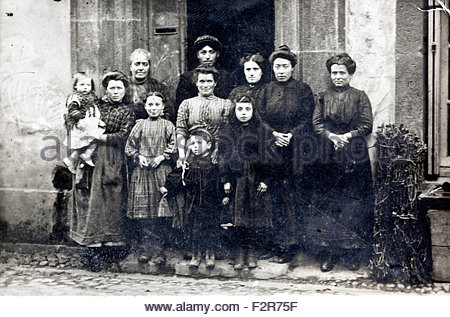 early 1900s 3 generation mainly female family standing in front of house France - Stock Photo