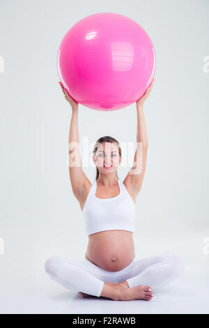 Portrait of a happy pregnant woman holding fitness ball on a head isolated on a white background - Stock Photo