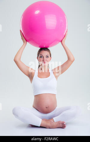 Portrait of a pregnant woman holding fitness ball on a head isolated on a white background - Stock Photo