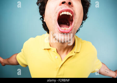 Young man is screaming with his mouth wide open - Stock Photo
