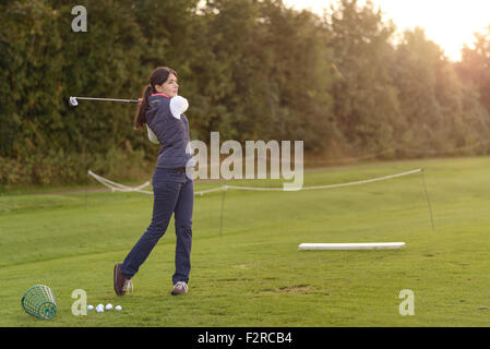 Female golfer standing on the driving range on a late afternoon day, standing in the finish position - Stock Photo